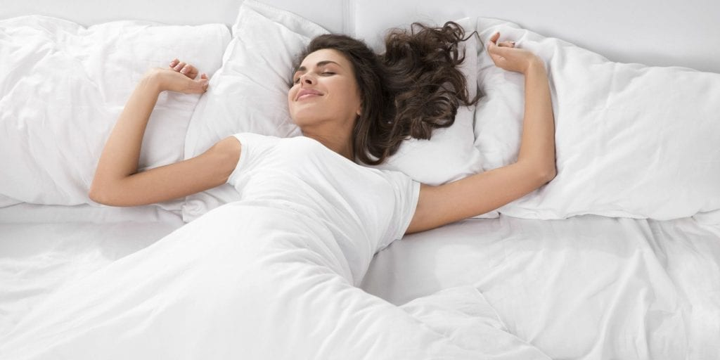 A woman enjoying sleep with the help of hypnosis for insomnia.